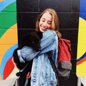 A white woman with blonde hair, Ciara, holds a small black puppy, Eddie, in front of a colorful background.